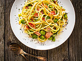 Spaghetti with bacon, broad bean and parmesan on wooden table