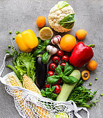 Fresh vegetables and fruits on eco string bag on a concrete background. Healthy lifestyle. Top view. Zero waste.