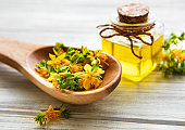 St. John's wort on the wooden spoon and natural oil