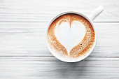 A cup of coffee with heart pattern on a table