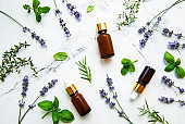 Bottles of essential oils with herbs and flowers