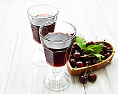 Cherry liqueur in a glass and fresh fruits