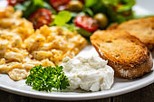 Continental breakfast -  cottage cheese, scrambled eggs, toasts and vegetables on wooden table