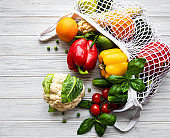 Fresh vegetables and fruits on eco string bag on a white wooden background. Healthy lifestyle. Top view. Zero waste.