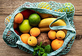 Mesh shopping bag with organic fruits on wooden background. Flat lay, top view. Zero waste, plastic free concept.  Summer fruits.