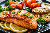 Fried salmon steak, fried potatoes and vegetables on wooden background