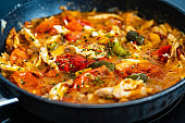 Chicken ragout with tomatoes, pepper and onion in cooking pan