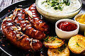 Fried sausages and vegetables on wooden table
