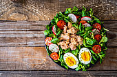 Tuna, boiled egg and vegetable salad  on wooden background