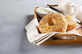 Bagels with cream cheese. Breakfast sandwiches on wooden tray on gray background. Copy space.