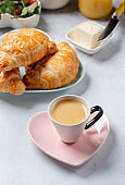 Cup of coffee and croissants on concrete background. French breakfast.