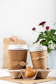 Two paper cups of coffee in cardboard tray on white background. Take out food. Cups with face of man and woman, couple in love, relations, love concept. Happy Valentine's day. Copy space.