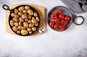 Roasted small whole potatoes in a cast iron skillet on concrete background. Top view, copy space, food background. Vegetarian or vegan food concept.