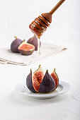 Juicy fresh fig fruits with honey on white background.