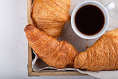 Cup of coffee croissants on wooden tray. Festive breakfast on white table. Top view, close-up.