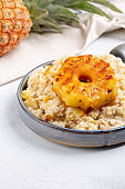 Sweet rice with grilled pineapples and raisins on gray plate on concrete background. Vegetarian food concept .