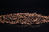 A pile of roasted coffee on a black background with reflection. The production of coffee.