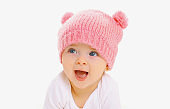 Portrait close up of sweet baby wearing a knitted pink hat over a white background