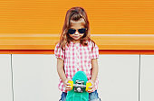 Portrait of stylish little girl child with skateboard in the city over an orange background