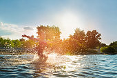 Happy child playing in the water at sunset. Summer vacation and healthy lifestyle concept.