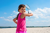 Portrait of happy child with a racket in hand on the beach. Beach badminton, Concept sports and outdoor games in the summer.