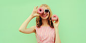 Portrait of smiling young woman covering her eye with two donuts on a green background