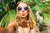 Summer portrait of woman stretching hand for taking selfie blowing lips sending sweet air kiss over palm tree background