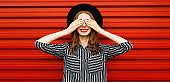 Portrait of smiling young woman covering her eyes with her hands wearing a black round hat, white striped shirt on red wall background