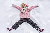 Little girl making snow angel outdoors in winter. Winter vacation and holidays.