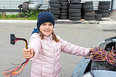 A child mechanic changes fuses in a car. Repair services in car service.