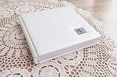 White photo book with leather cover. Stylish wedding photo album.  Family photoalbum on the table . Beautiful notepad or photobook with elegant openwork embossing on a wooden background.