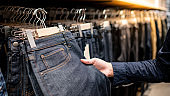 Male hand choosing black jeans