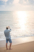 Asian man tourist standing on the beach looking at sunset