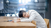 Asian man student taking a nap in college library