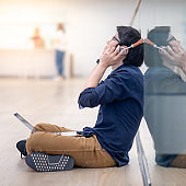 Asian man listening to music  sitting on the floor with laptop