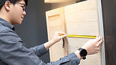 Asian man using tape measure on cabinet material