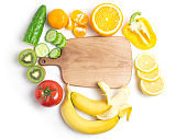 Various vegetables and fruits around the cutting Board on a white background, top view. The concept of healthy eating, food background. Vegetable border with space for text. Vegan, vegetarian.