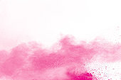 Pink color powder explosion on white background.