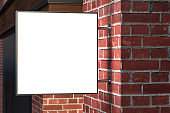 Square signboard or signage on the red brick wall with blank white sign mock up. Night scene. Side view.