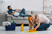 Sexism and disrespect for wife. Man lies on couch and typing on phone, sad woman clings to her head and washes floors