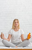 Attractive woman sitting in lotus position and holding two detox cocktails