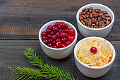 Sauerkraut or fermented cabbage with cranberries and pine nuts on rustic wooden background. The concept of healthy eating. Organic and vegetarian food, fermentation ingredients. Close up, copy space for text