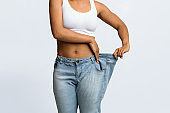 Young black woman wearing too large jeans