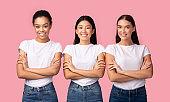 Three Multiethnic Women Posing Crossing Hands Over Pink Background, Studio