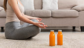 Woman doing yoga at home and sitting in lotus position