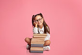 Start learning concept. Little girl in glasses and uniform, sits near stack of books