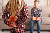 Unrecognizable Girl Holding Gift For Brother Standing At Home, Cropped