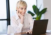 Smiling Mature Woman At Laptop Browsing Internet In Modern Office