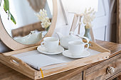Free time at home and hot drink. Tea in kettle, cups for two on tray with notepad or book on wooden cosmetic table