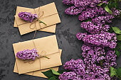 Spring celebration background, lilac and craft envelopes top view